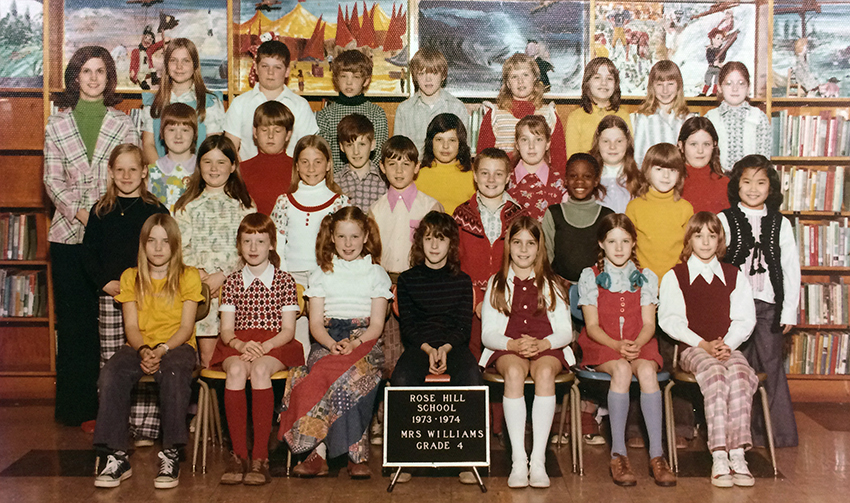 Color class photograph from the 1973 to 1974 school year showing Mrs. Williams' fourth grade class. There are 30 students pictured, mostly girls. Nearly all of the children are Caucasian except for one African-American child and one Asian child. Mrs. Williams is standing in the back left corner. She is wearing a pink, black, and white striped jacket over a green turtleneck shirt.