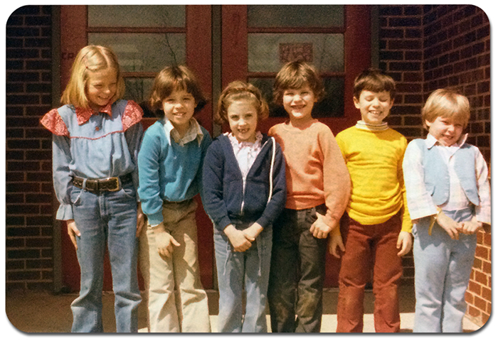 Color photograph, taken around 1980, showing six children standing in front of the main entrance to Rose Hill Elementary School. The children are smiling and giggling.