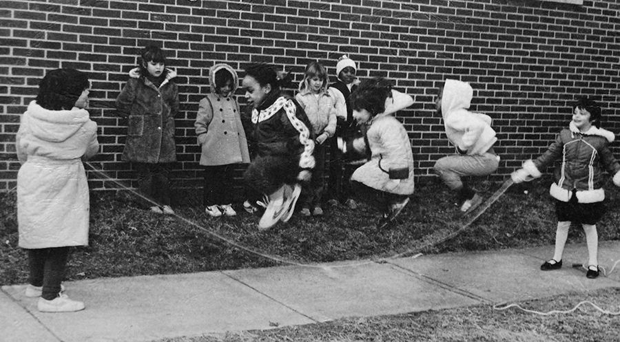 Black and white photograph from the cover of Rose Hill Elementary School's 1982 to 1983 yearbook showing a group of students playing jump rope on the sidewalk. Ten girls are pictured, five of whom are waiting along the wall for their turn. Three girls are in mid-air as two other girls swing the rope beneath them.