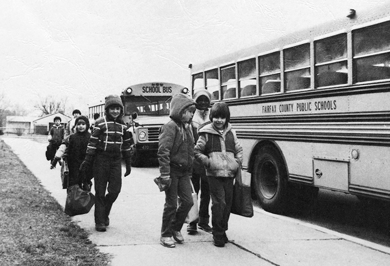 Black and white photograph from the cover of Rose Hill Elementary School's 1983 to 1984 yearbook showing a group of students walking up the sidewalk toward the entrance of the school after having been dropped off by their school buses. Two buses are visible on the right.