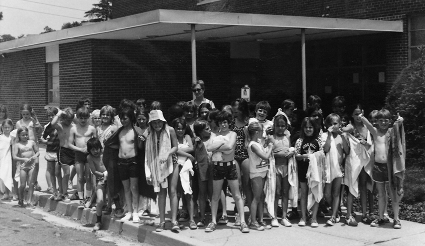 Black and white photograph of a group of about 41 students, boys and girls, standing in front of the entrance to Rose Hill Elementary School. The children are wearing bathing suits and holding towels. A female teacher is standing at the back of the group.