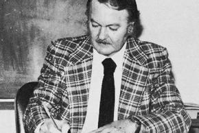 Black and white yearbook portrait of Principal Joseph Hucks taken in 1978. He is seated at his desk signing a piece of paper.
