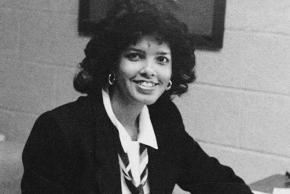 Black and white yearbook portrait of Principal Sandra Culmer taken in 1985. She is seated at her desk.