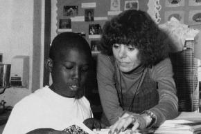 Black and white yearbook portrait of Principal Marcy Mager taken in 1991. She is pictured with a student, leaning over his desk looking at his work. He appears to be describing or reading something to her.